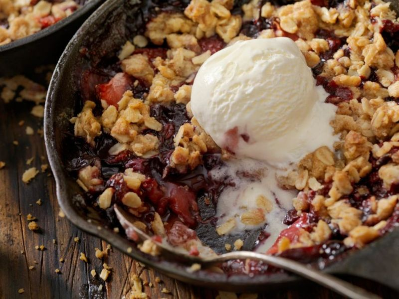 Strawberry and Blueberry Crisp with Vanilla Ice Cream in a Cast Iron Skillet