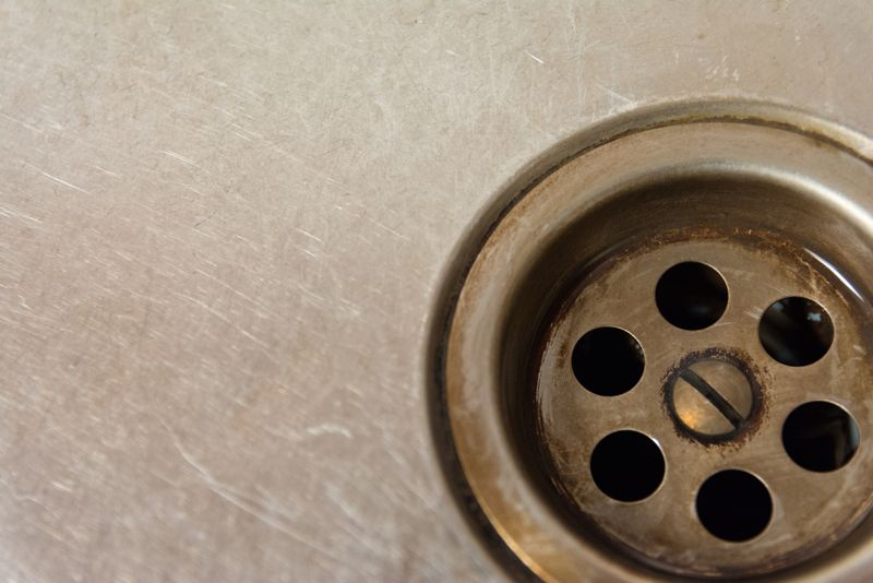 Close up of a drain hole in a dirty sink