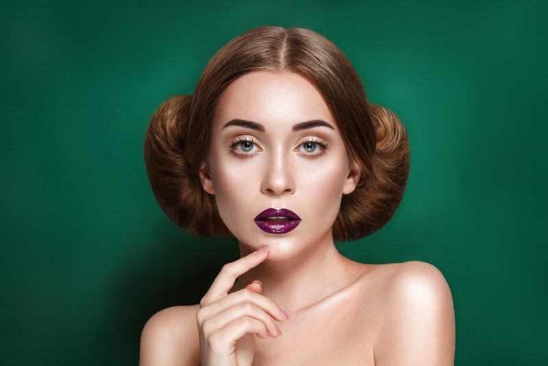 Attractive mysterious young woman with double hair bun in Princess Leia hairstyle looks towards the camera