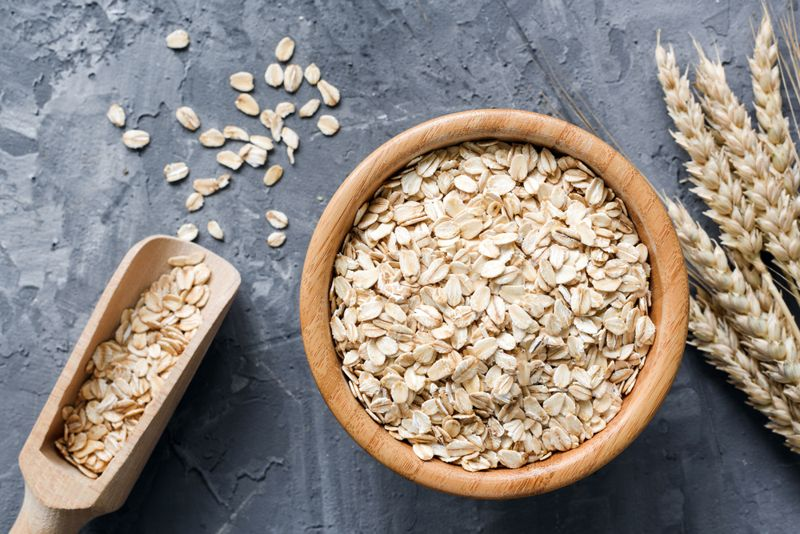 Rolled oats or oat flakes in wooden bowl