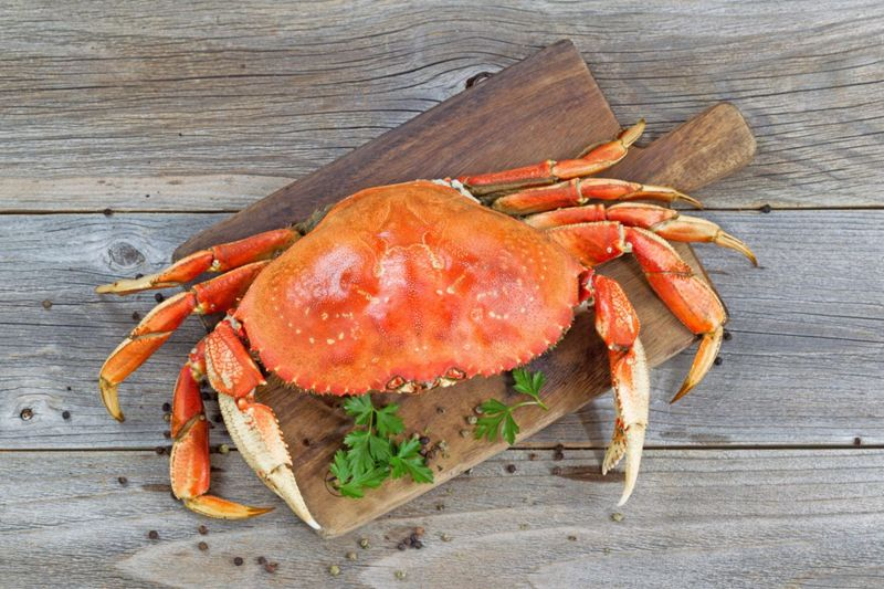 Top view of a steamed Dungeness crab on wooden server board with herbs and spices ready to eat