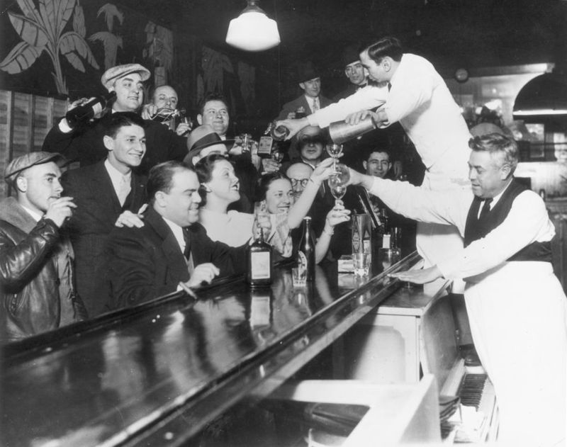 Bartenders at Sloppy Joe's bar pour a round of drinks on the house for a large group of smiling customers