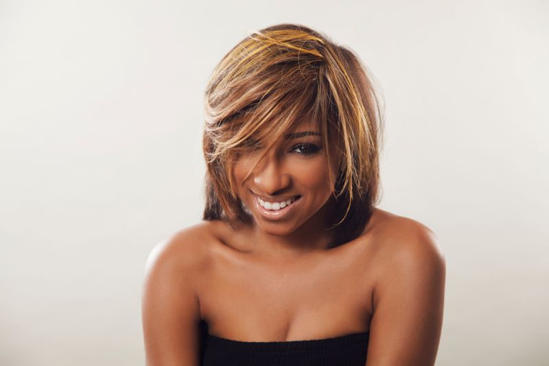 An African American female with caramel highlights smiling