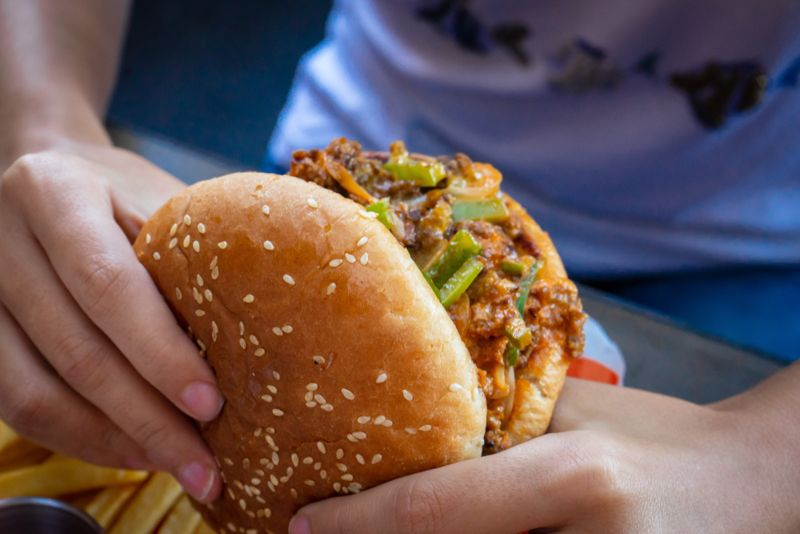 Woman's hands eating a ground beef burger in a restaurant.