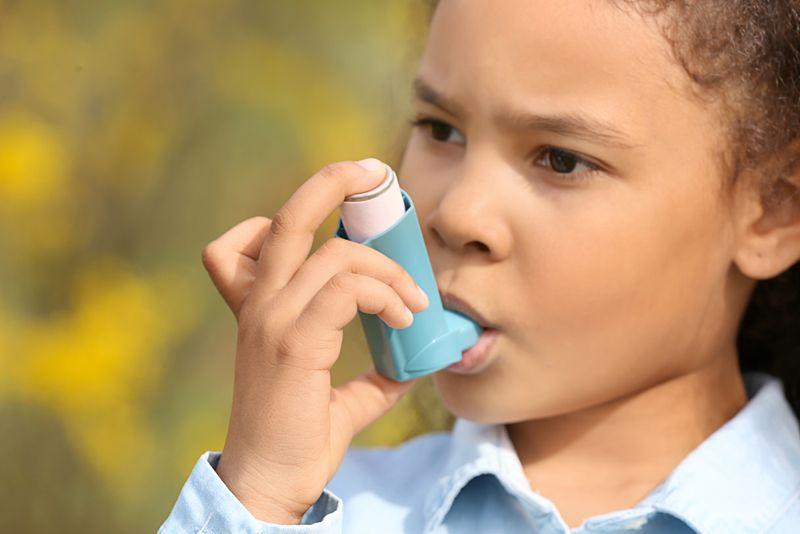 little girl using her asthma inhaler