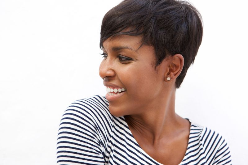 Close up portrait of a young african american woman smiling and looking away