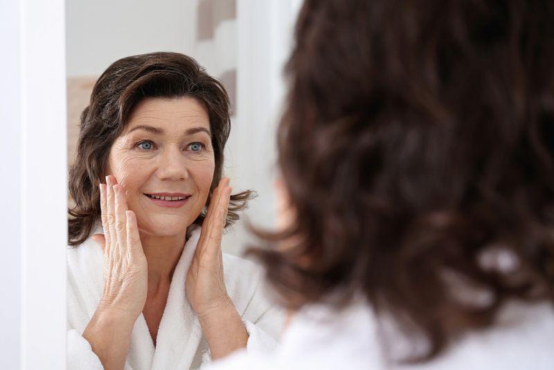 senior woman looking at mirror