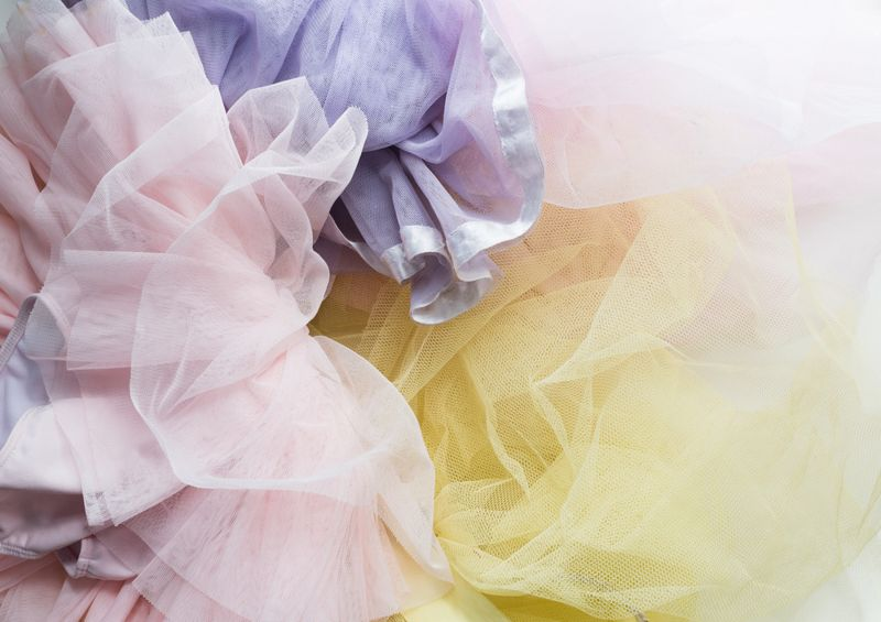 High angle full frame view of little girl's pink, purple and yellow tutus in a pile