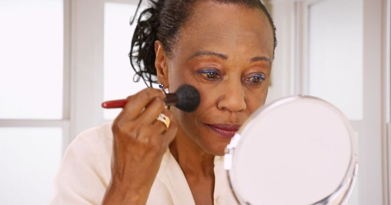An elderly black woman does her makeup in the morning in her bathroom