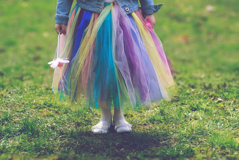 Little girl in colorful tutu skirt standing on green grass while holding magic wand