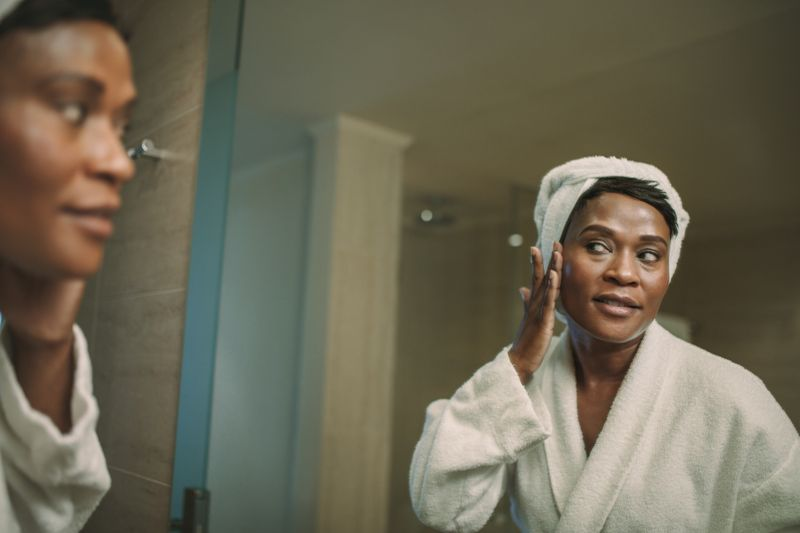 Mature woman in bathrobe putting on cream on her face skin