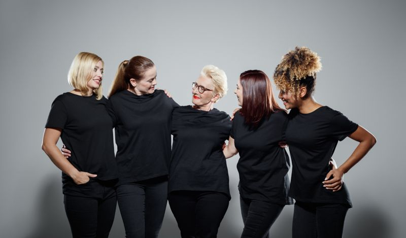 Smiling multi-ethnic women wearing black clothes. Powerful females are standing arm around against gray background. They are supporting Me Too movement.