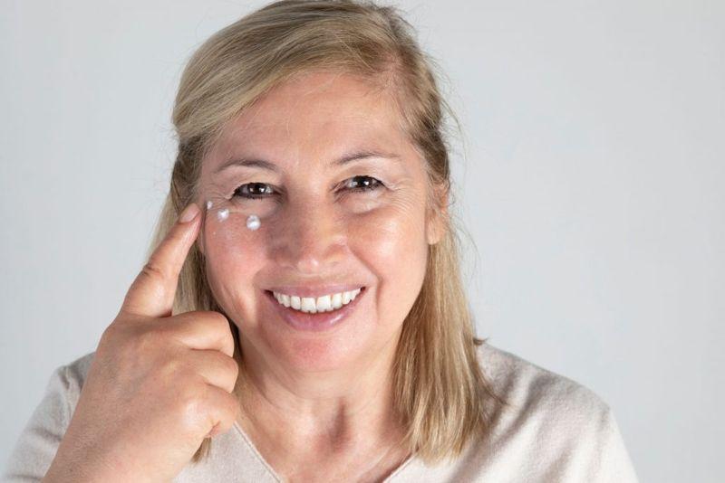 Senior woman applying night cream, isolated on gray background.