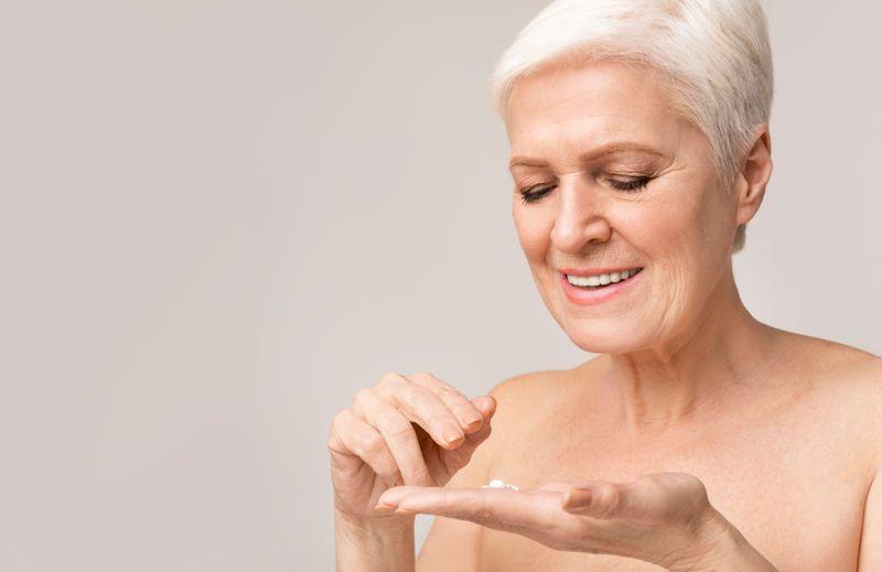 Happy senior woman applying anti-wrinkle cream for skin