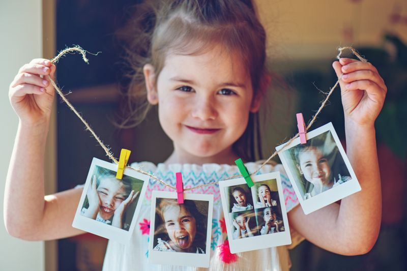 Four years old little girl holding string of instant photos