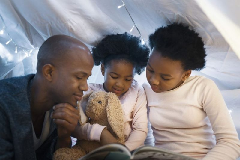 father reading with daughters