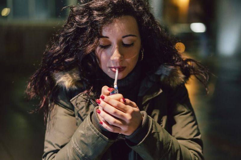 woman lighting cigarette
