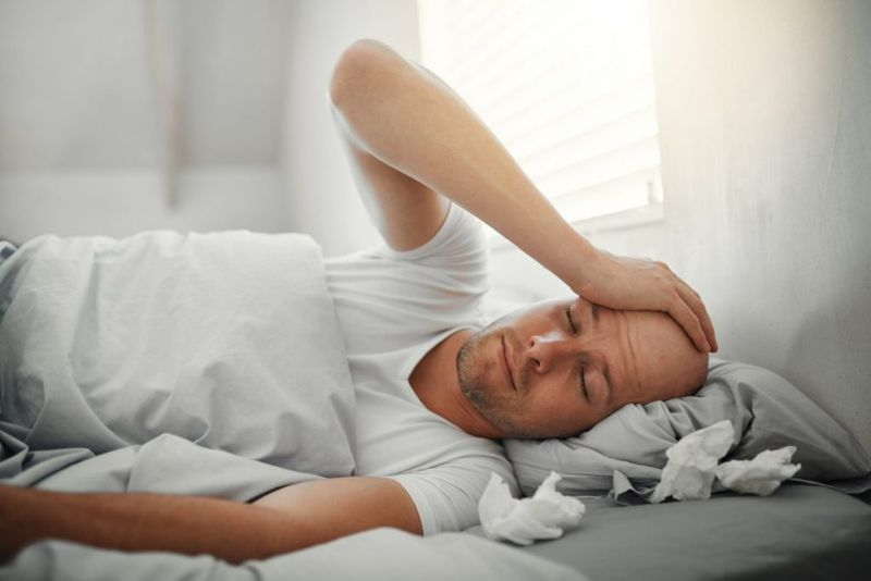 man in bed holding his head in pain