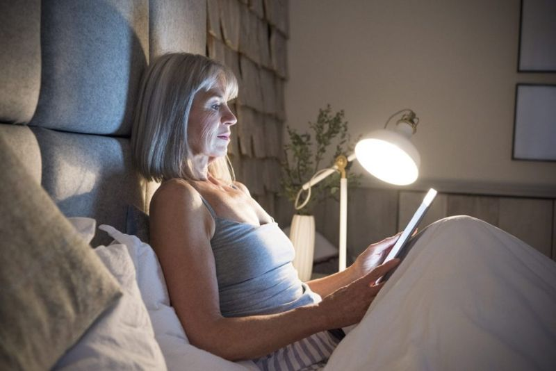 woman in bed reading