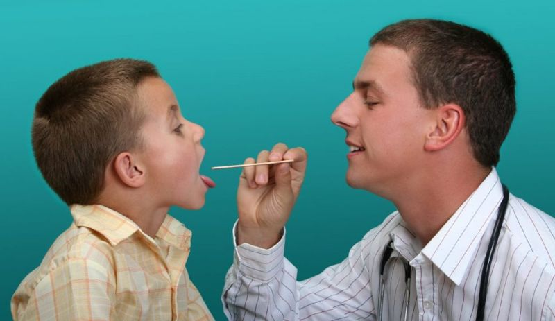 doctor checking a child's tonsils