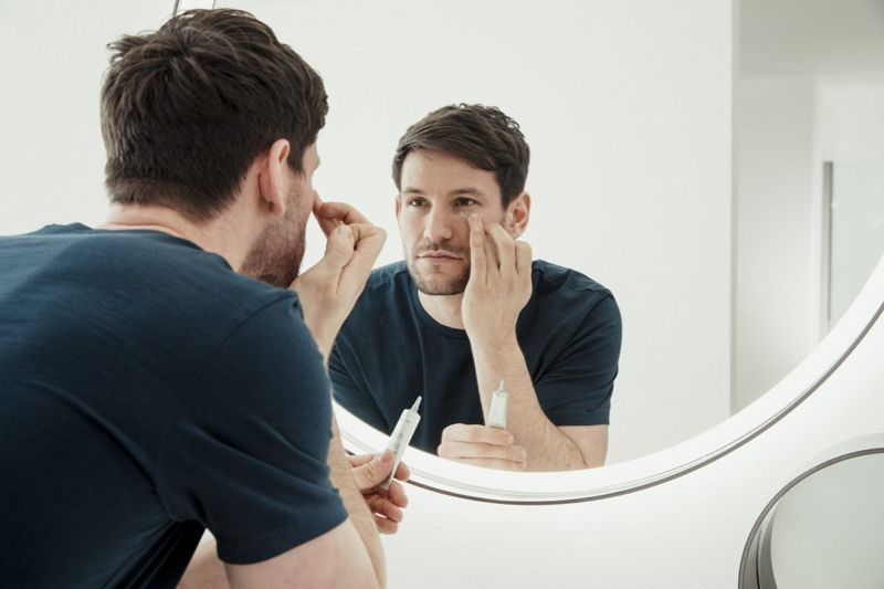 Man looking in mirror at skin