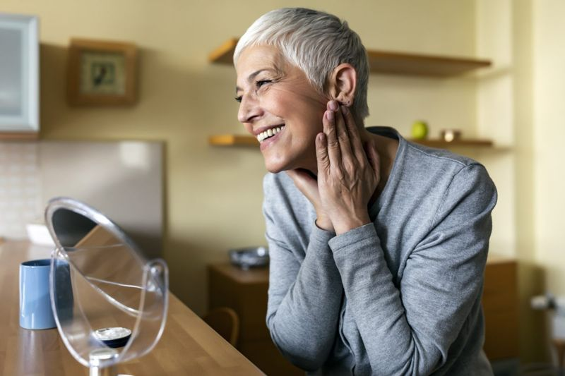 Elderly woman smiling in the mirror