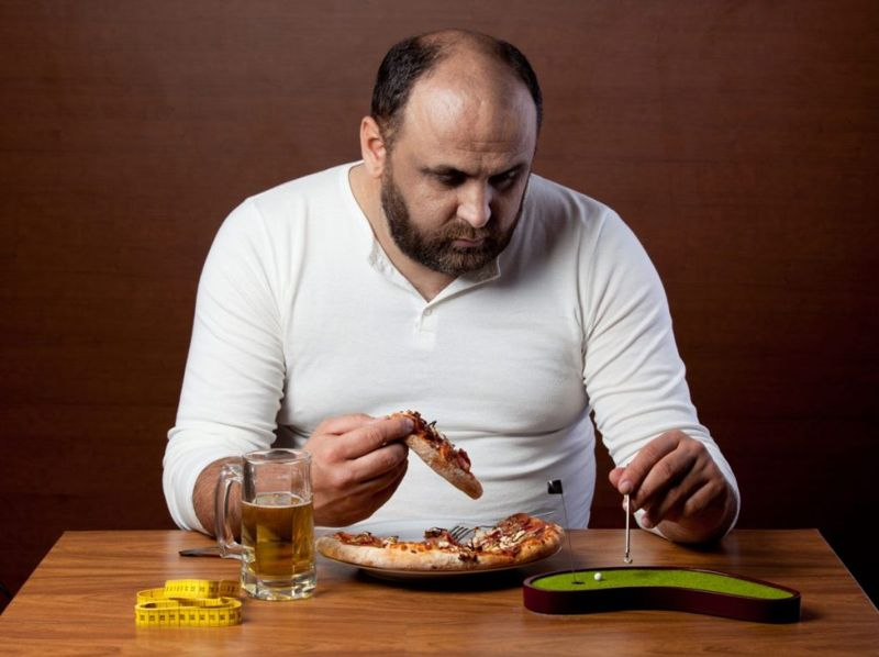 Overweight man eating pizza