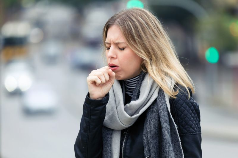 woman coughing street