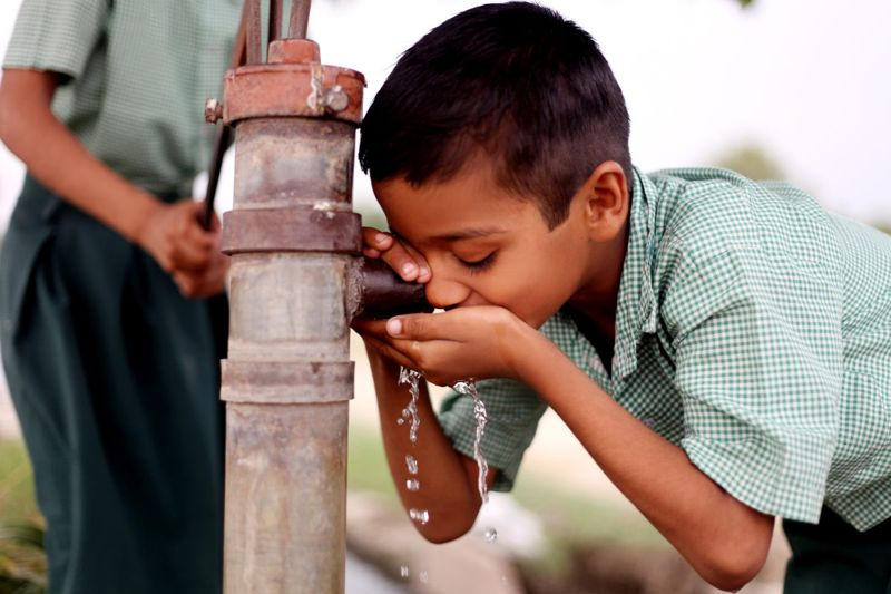 boy drinking from water pump