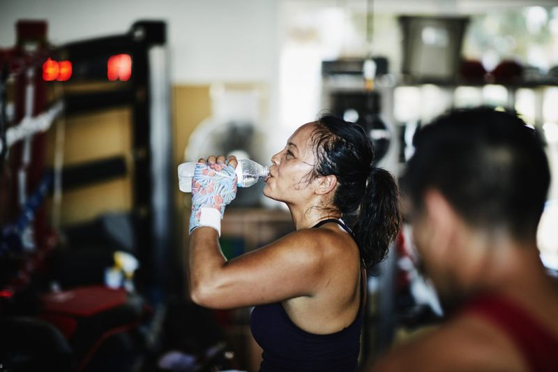 Sweating female boxer drinking water after workout in boxing gym