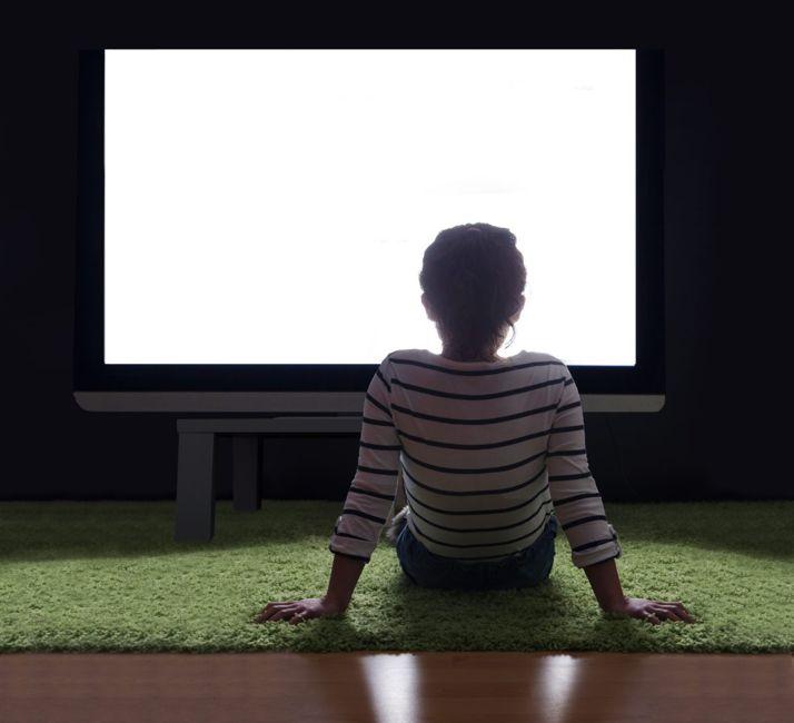 Girl watching TV in the dark