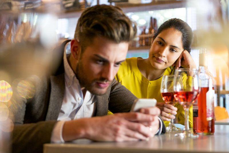 Guy ignoring woman on date