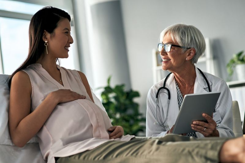 Woman and doctor discussing pregnancy.