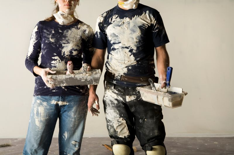 Couple doing plaster, mid section