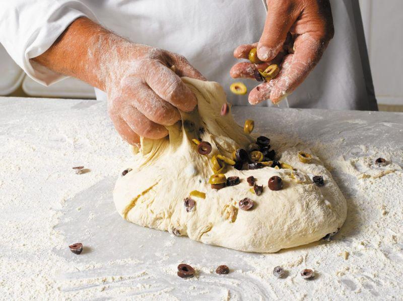 Baker adding olives to dough