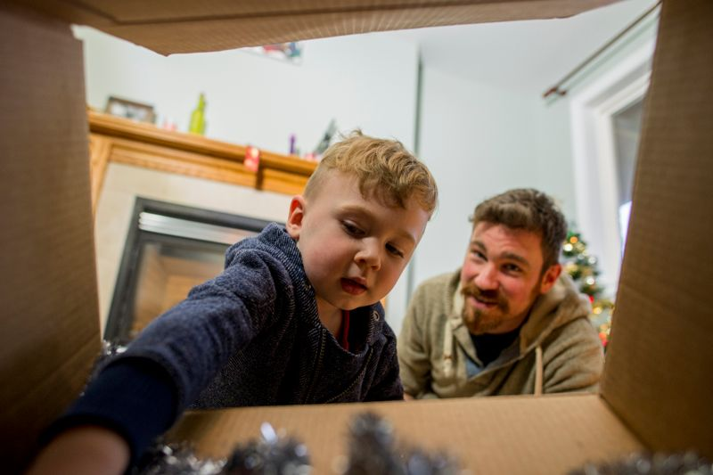 Cute little boy reaching into a cardboard box full of ornaments while decorating a Christmas tree with his father in an apartment on Christmas eve.