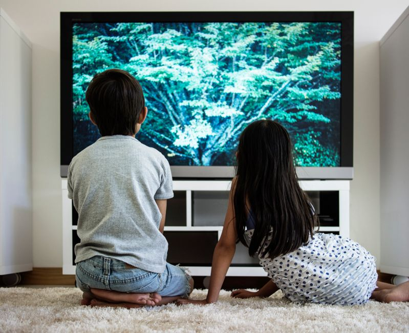 Boy and girl watch television with images of gree tree, sitting in a hite room.