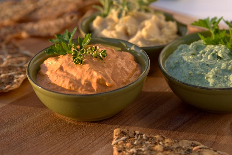 Roasted red bell pepper and vegetable herb hummus on a table