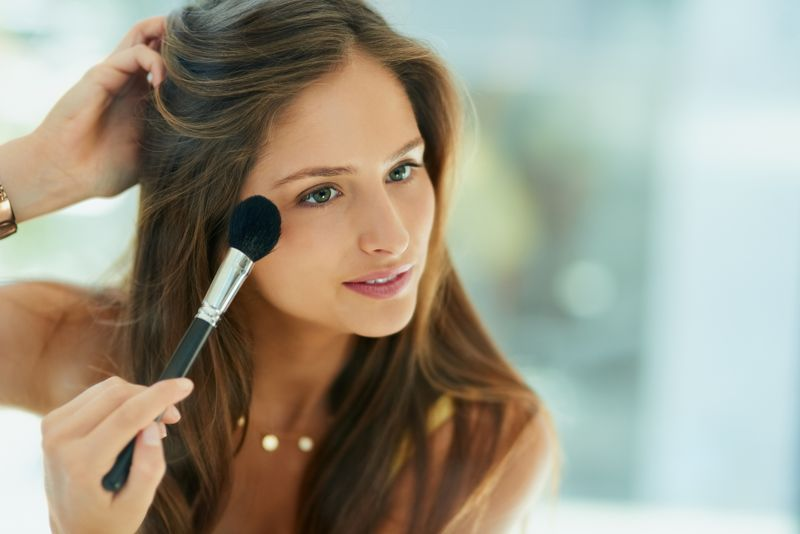 Shot of an attractive young woman applying makeup to her face with a brush
