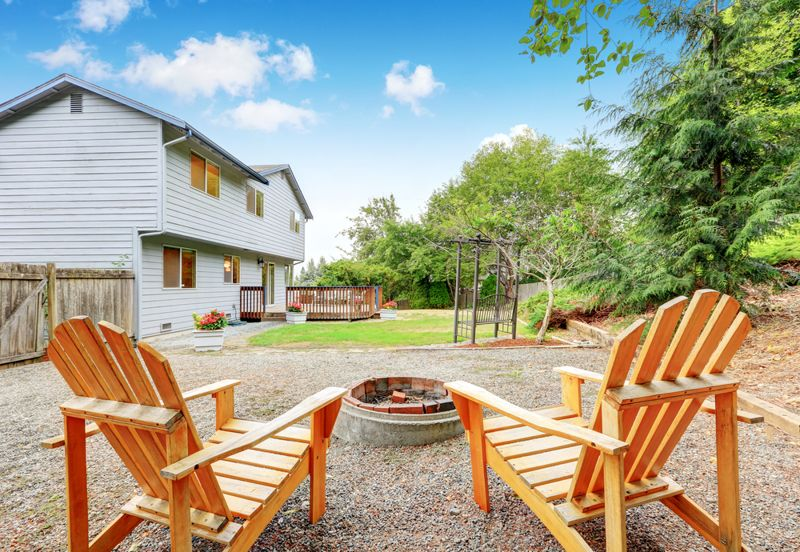 Two lawn chairs with fire pit at the backyard
