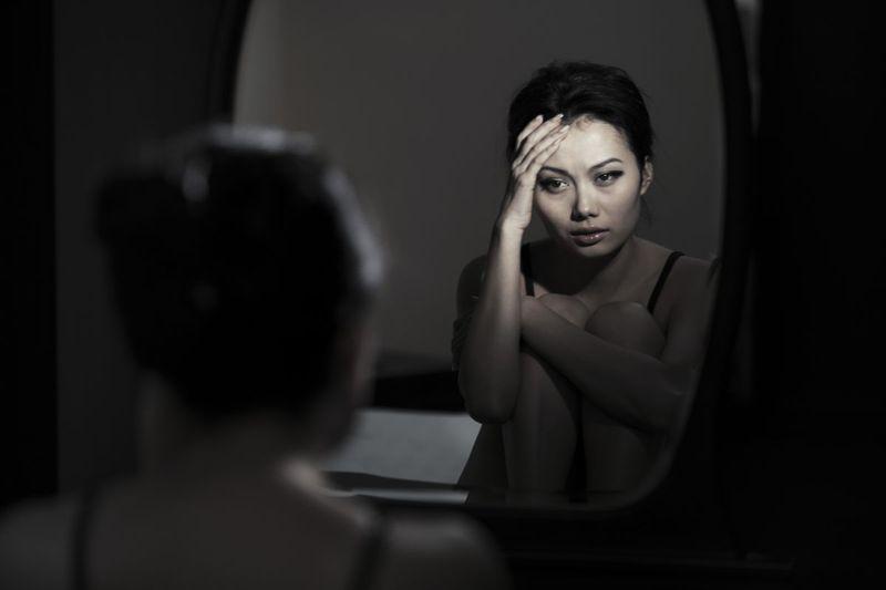 sad adult female with mirror