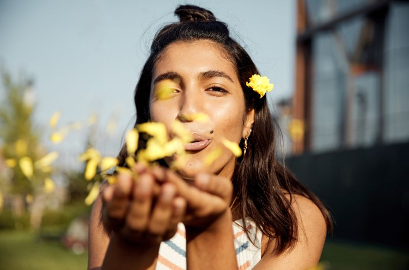 Portrait of young woman blowing kiss of flowers
