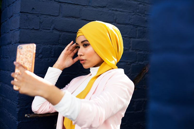 Young Muslim woman using phone