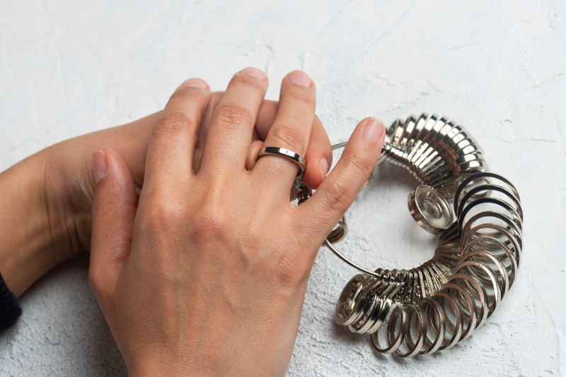 Jeweler checking ring finger size of female client.