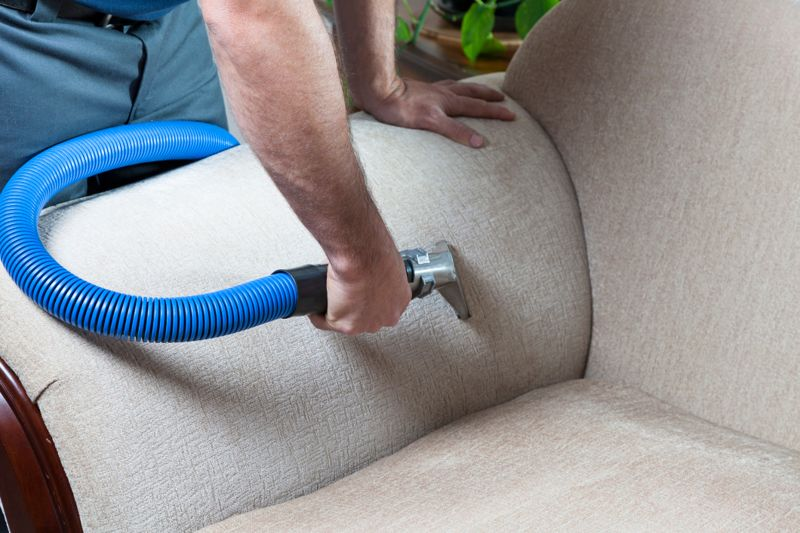 Man cleaning sofa with steam cleaning in home