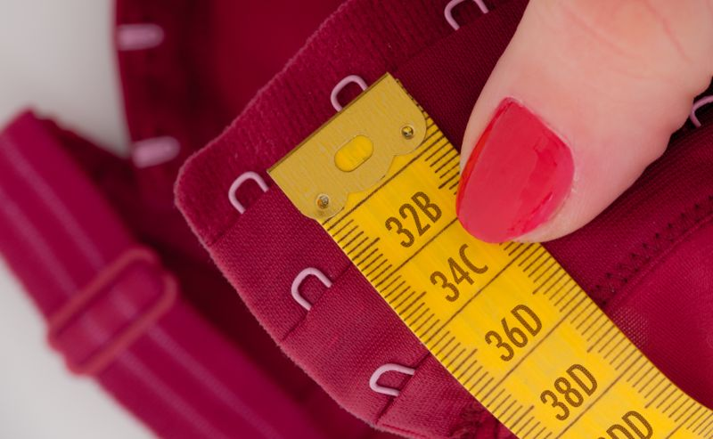 close up of a  scale with american/uk  bra sizes and a dark red bra in the background. The tape measure shows bra and cup sizes