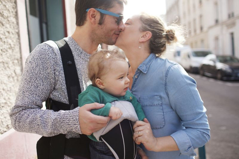 A 8 months old baby boy with his parents in the street