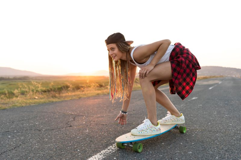 Beautiful young woman skateboarding on country road, at sunset.