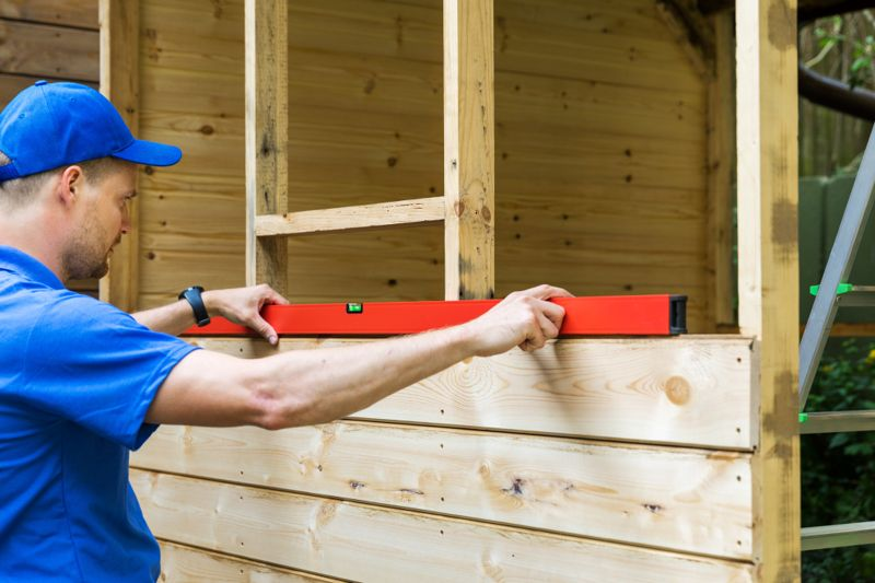 shed construction - worker check the level of wooden plank wall