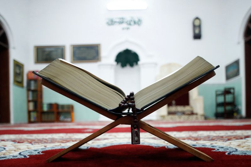 An open Holy Quran and muslim prayer beads on wood stand with mihrab in background.